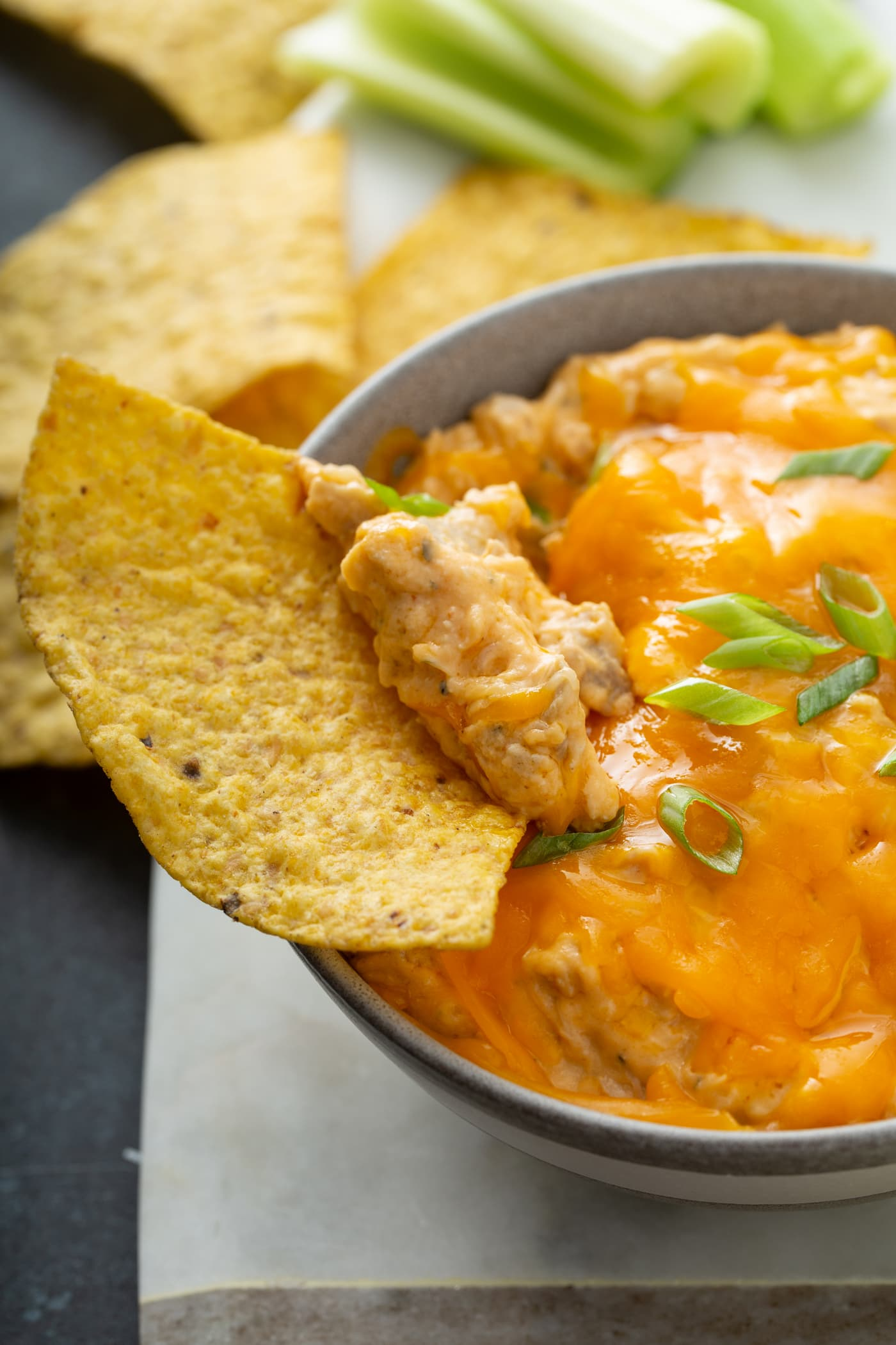 A chip being dipped into warm buffalo chicken dip. Cheese is melted on top, and there are chopped green onions sprinkled over the dip.