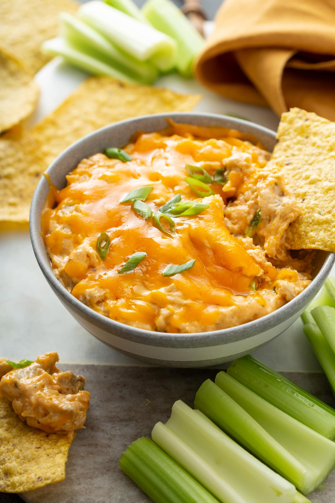 A bowl of buffalo chicken dip topped with melted cheese and chopped green onions. A chip is being dipped into it. There are chips and celery sticks surrounding the bowl of dip.