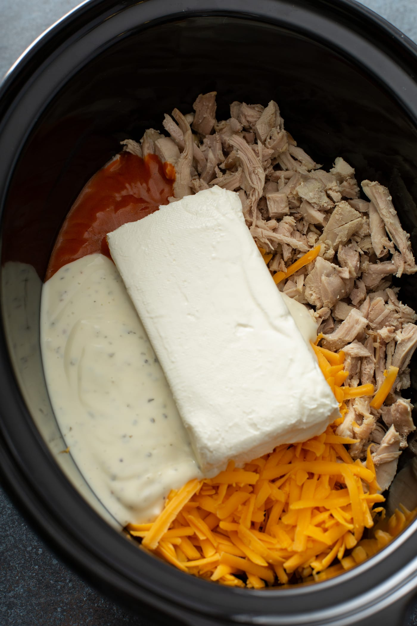 A slow cooker containing shredded chicken, cheese, cream cheese, ranch dressing and buffalo sauce.