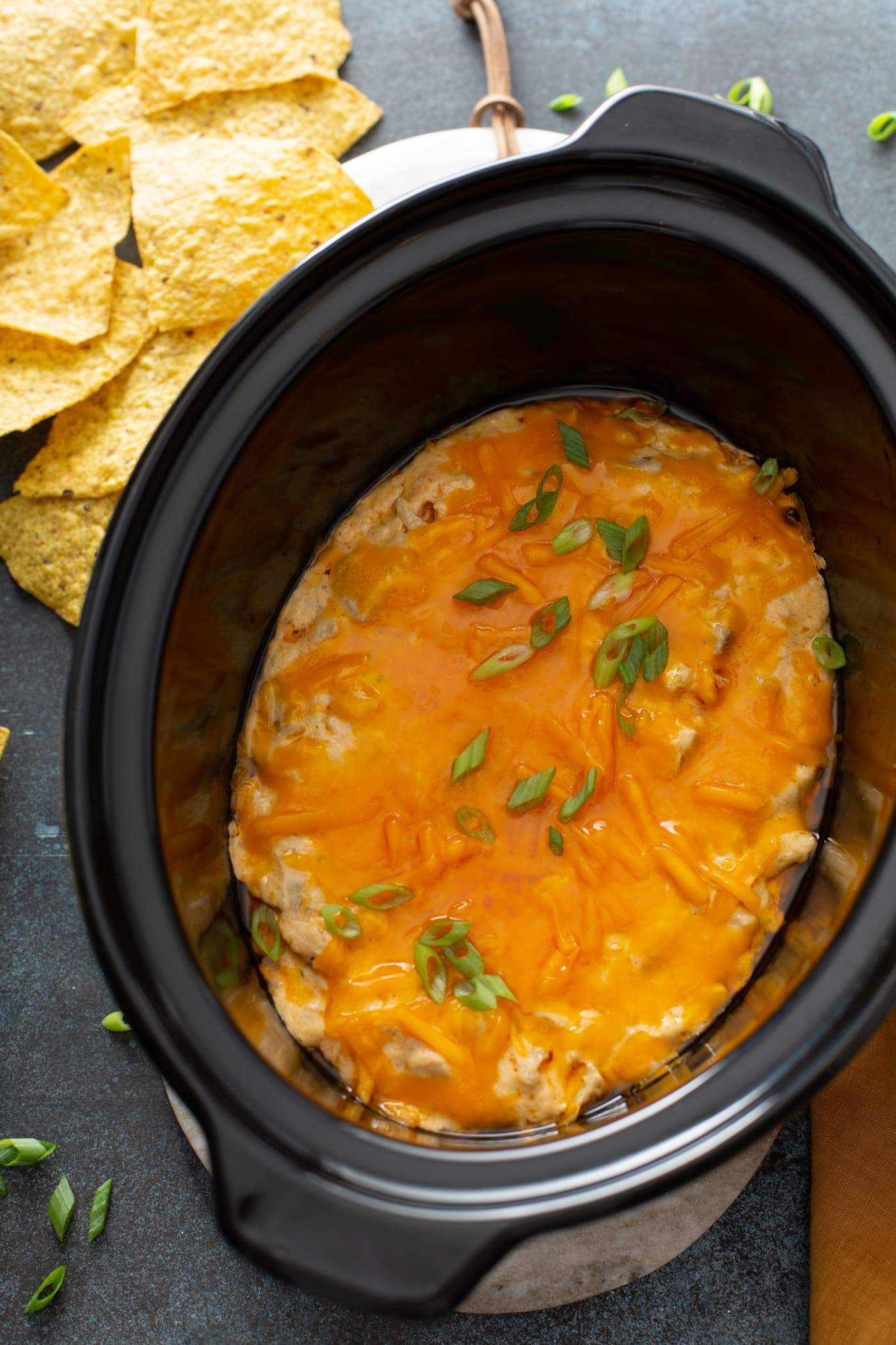 A slow cooker filled with buffalo chicken dip. The dip is cooked to a smooth, creamy perfection with melted cheese on top. Tortilla chips are in the background.