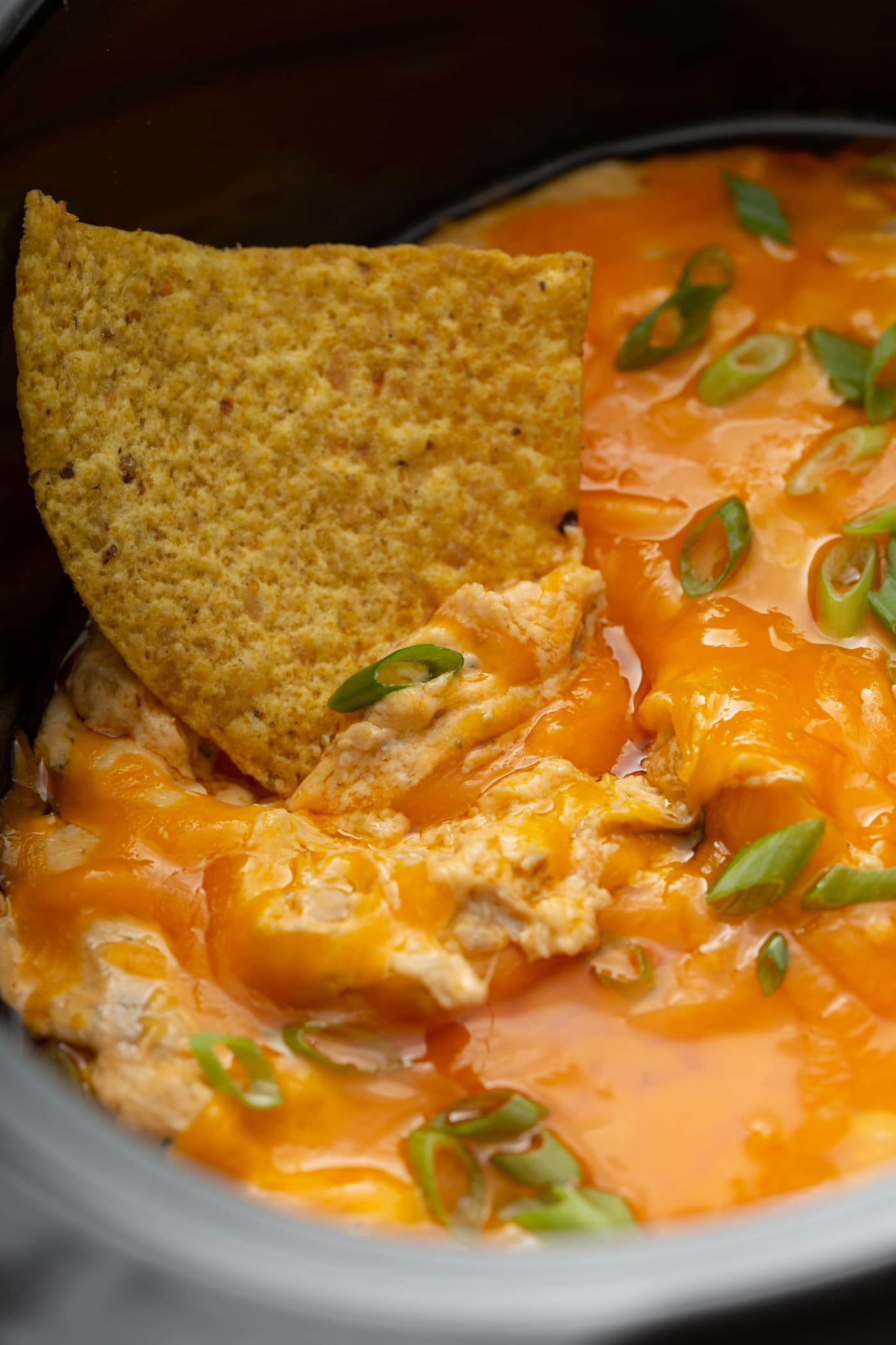A tortilla chip with slow cooker buffalo chicken dip on it. There is shredded chicken, creamy buffalo sauce and chopped green onions in the dip.