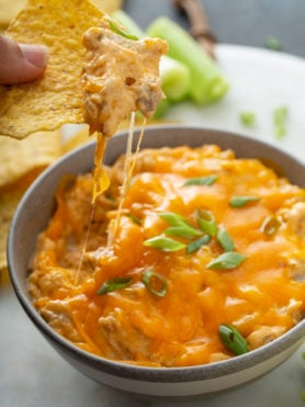 A bowl of buffalo chicken dip. A chip has been dipped in and melty stringy cheese is hanging from the tip of the chip. Chips and celery sticks are in the background.