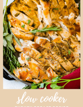 A photo of sliced juicy slow cooker turkey breast garnished with fresh herbs.