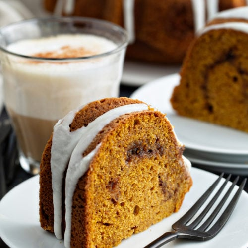 A slice of sour cream cinnamon swirl pumpkin bundt cake on a dessert plate with a fork on the plate next to the cake. The cake has a drizzle of white glaze on top. another slice of cake on a dessert plate, and the rest of the bundt cake on a cake platter are in the background.