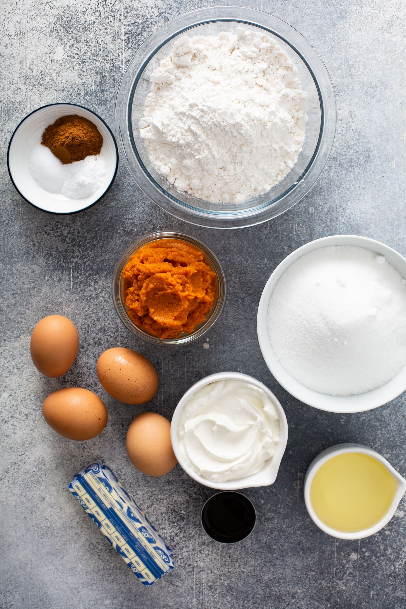Small containers with ingredients for sour cream cinnamon swirl pumpkin bundt cake. There are containers of flour, sugar, sour cream, butter, pumpkin, and cinnamon. there are also four brown eggs on the table.