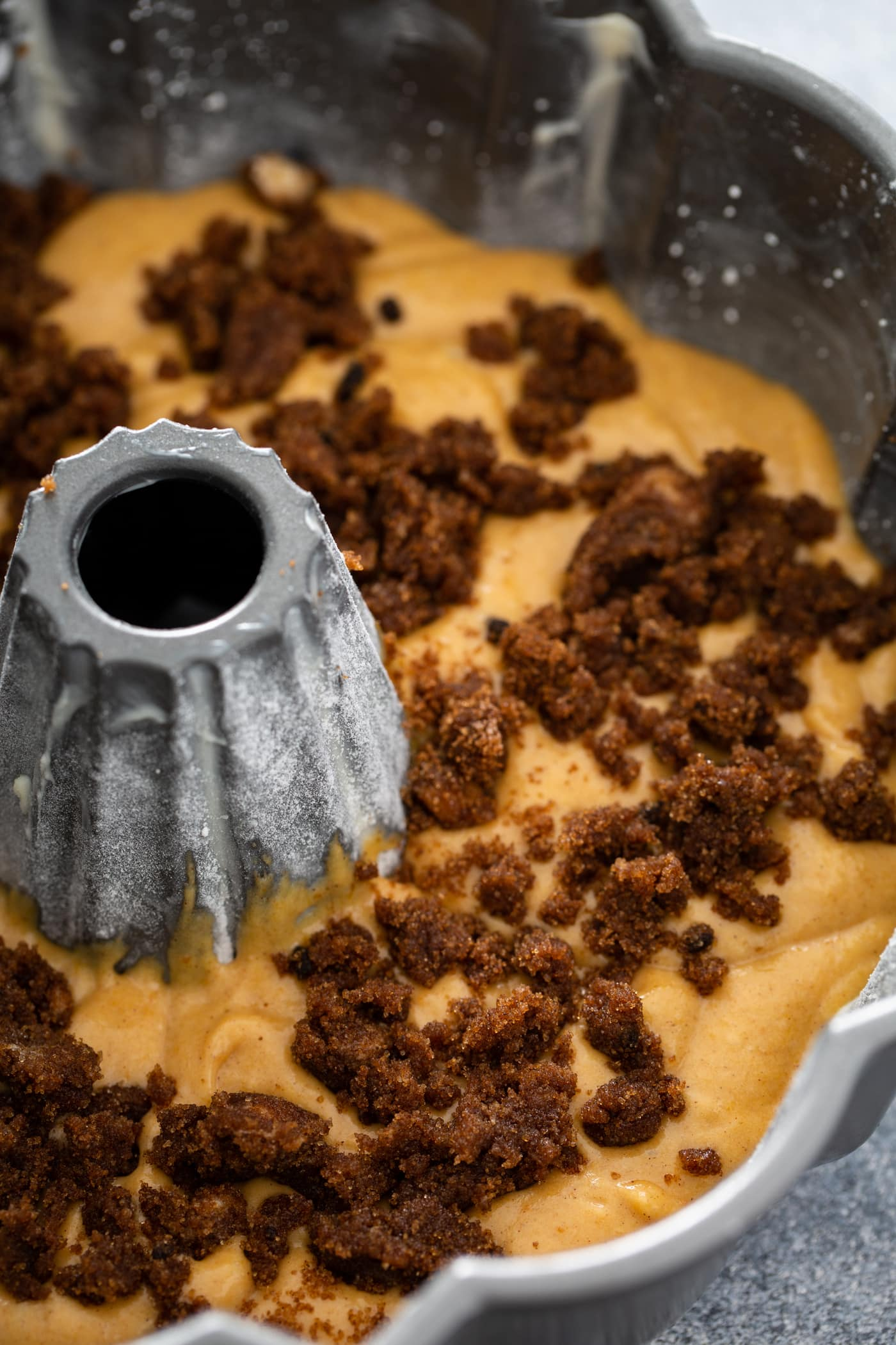 An unbaked pumpkin bundt cake in a bundt pan with cinnamon filling on top.