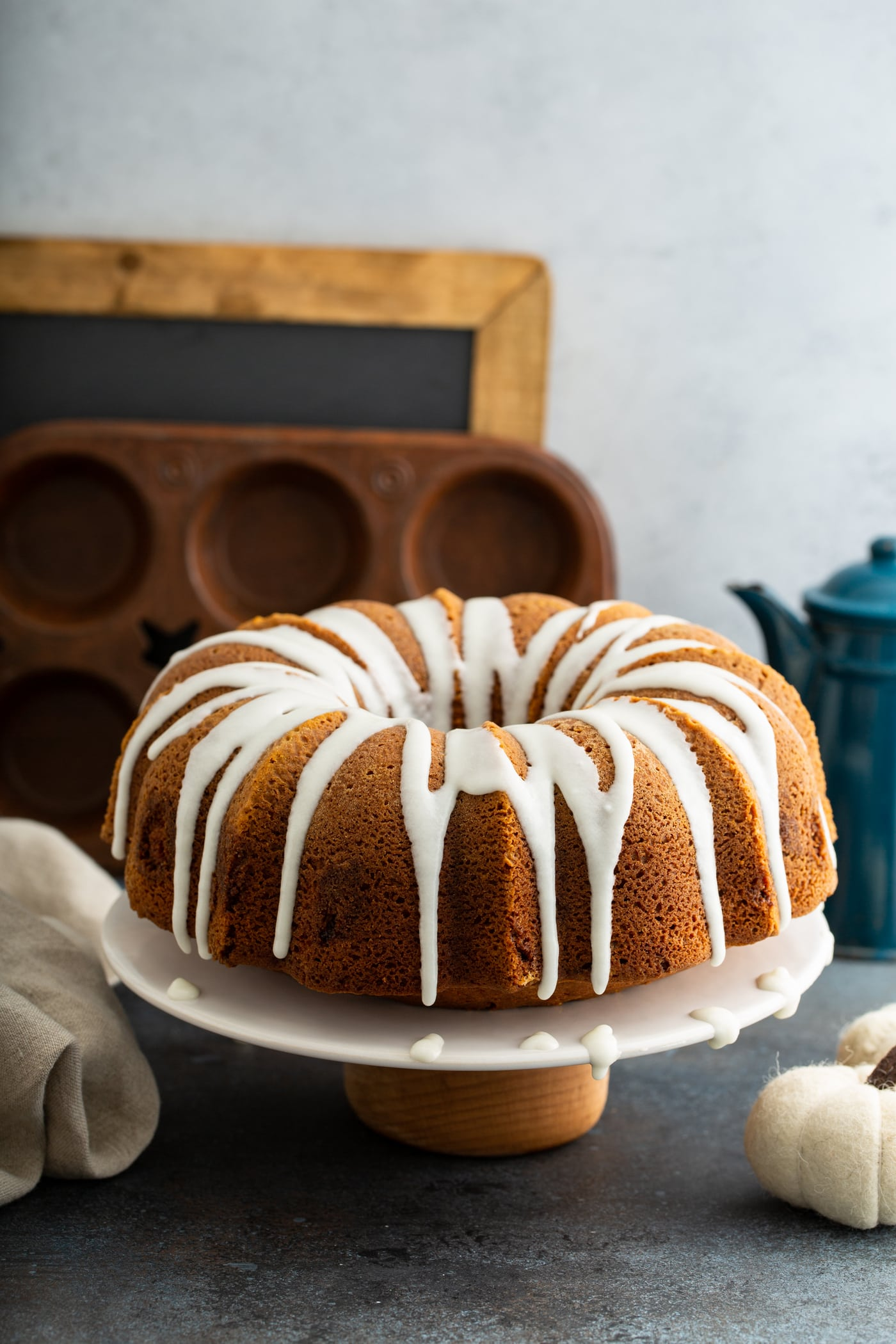 A sour cream cinnamon swirled pumpkin bundt cake with white glaze drizzled over the top. The cake is on a white cake plate and a muffin tin, chalk board, and coffee pot are in the background.