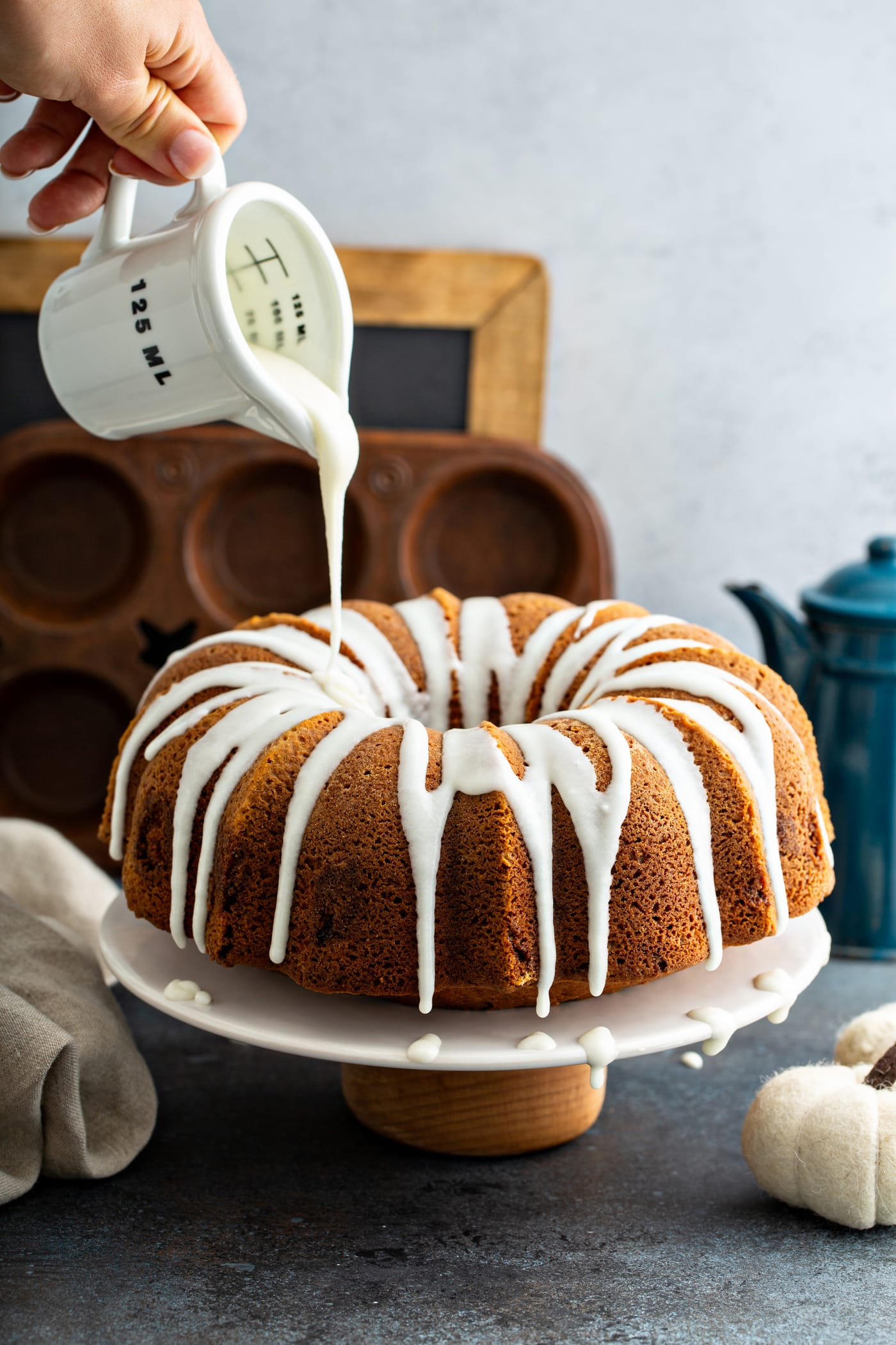 White glaze being drizzled from a glass measuring cup over the top of a sour cream cinnamon swirled pumpkin bundt cake. A muffin tin, a chalk board, and a blue coffee pot are in the background.
