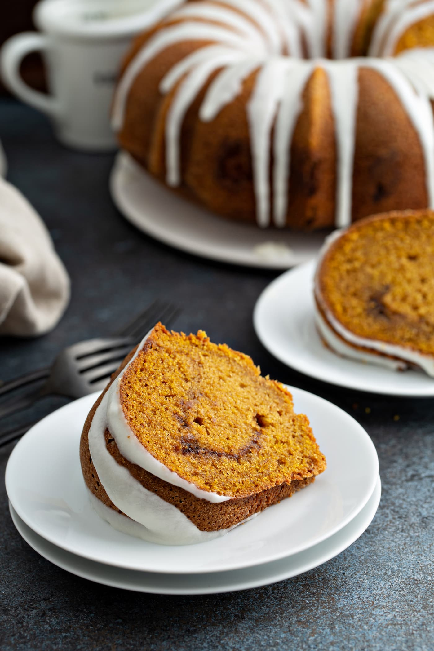 Two slices of sour cream cinnamon swirl pumpkin bundt cake on dessert plates. The cinnamon swirl center is visible and the cake top is drizzled with white glaze. The rest of the bundt cake with glaze drizzled over the top is in the background. A fork and napkin are next to one of the dessert plates.