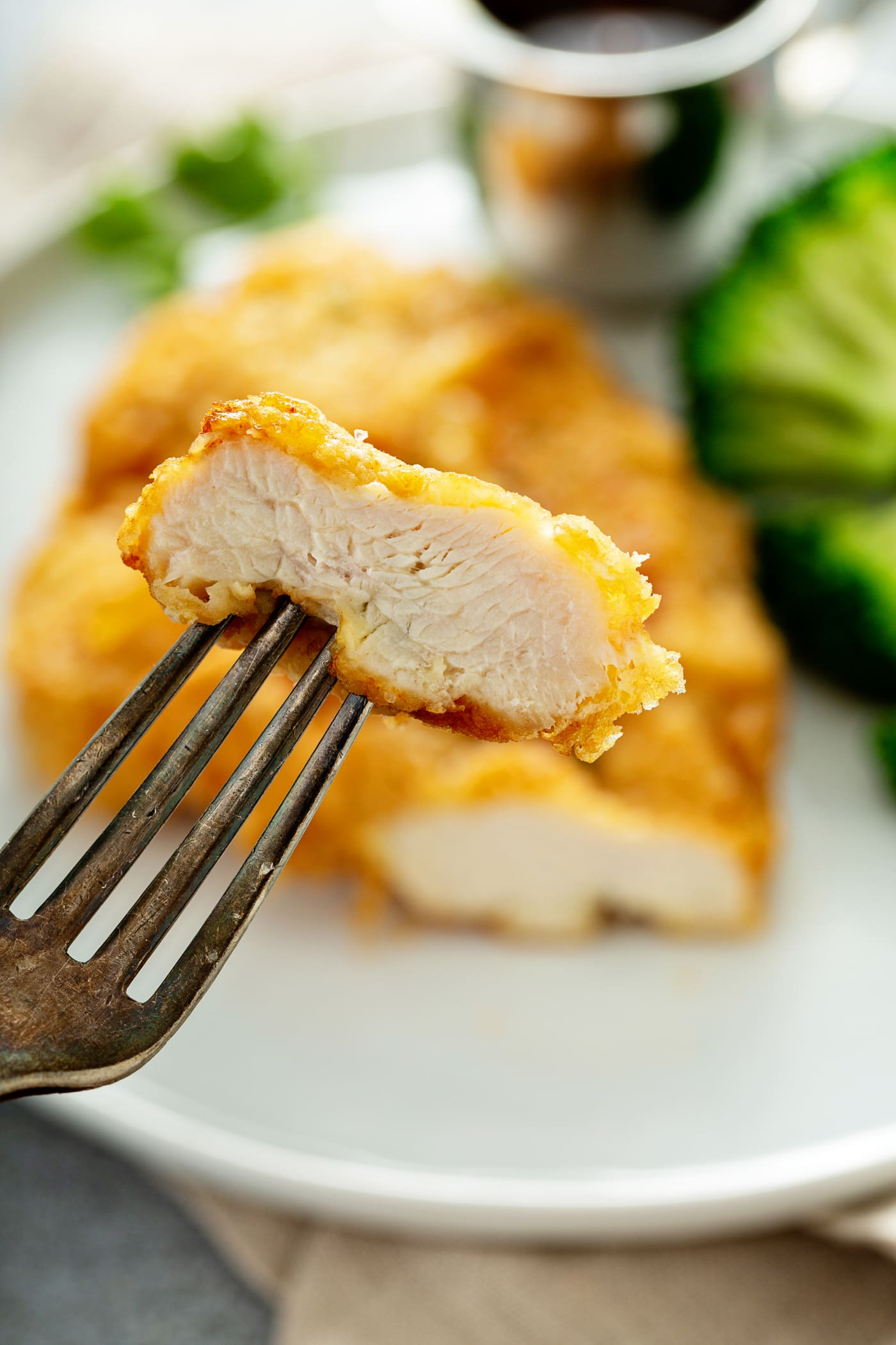 A golden brown fried chicken breast with a slice cut off and held up in the tines of a fork. There is broccoli beside the chicken on the plate.