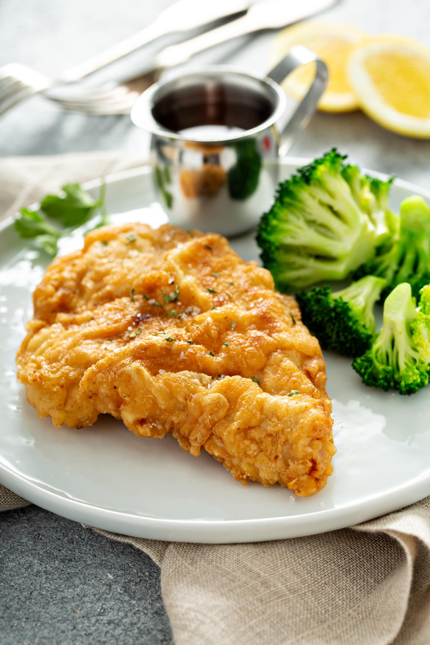 A piece of chicken fried to a perfect golden brown. There is a silver pitcher of sauce and steamed broccoli next to the chicken on a white dinner plate.