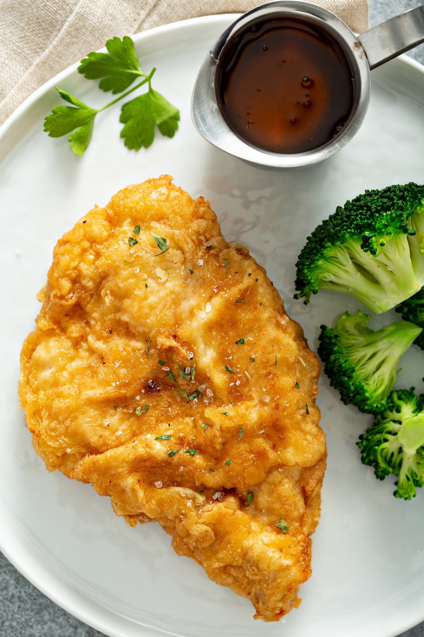 A chicken breast that has been fried to a golden brown, resting on a white dinner plate. There is also steamed broccoli next to the chicken and a small pitcher of sauce.