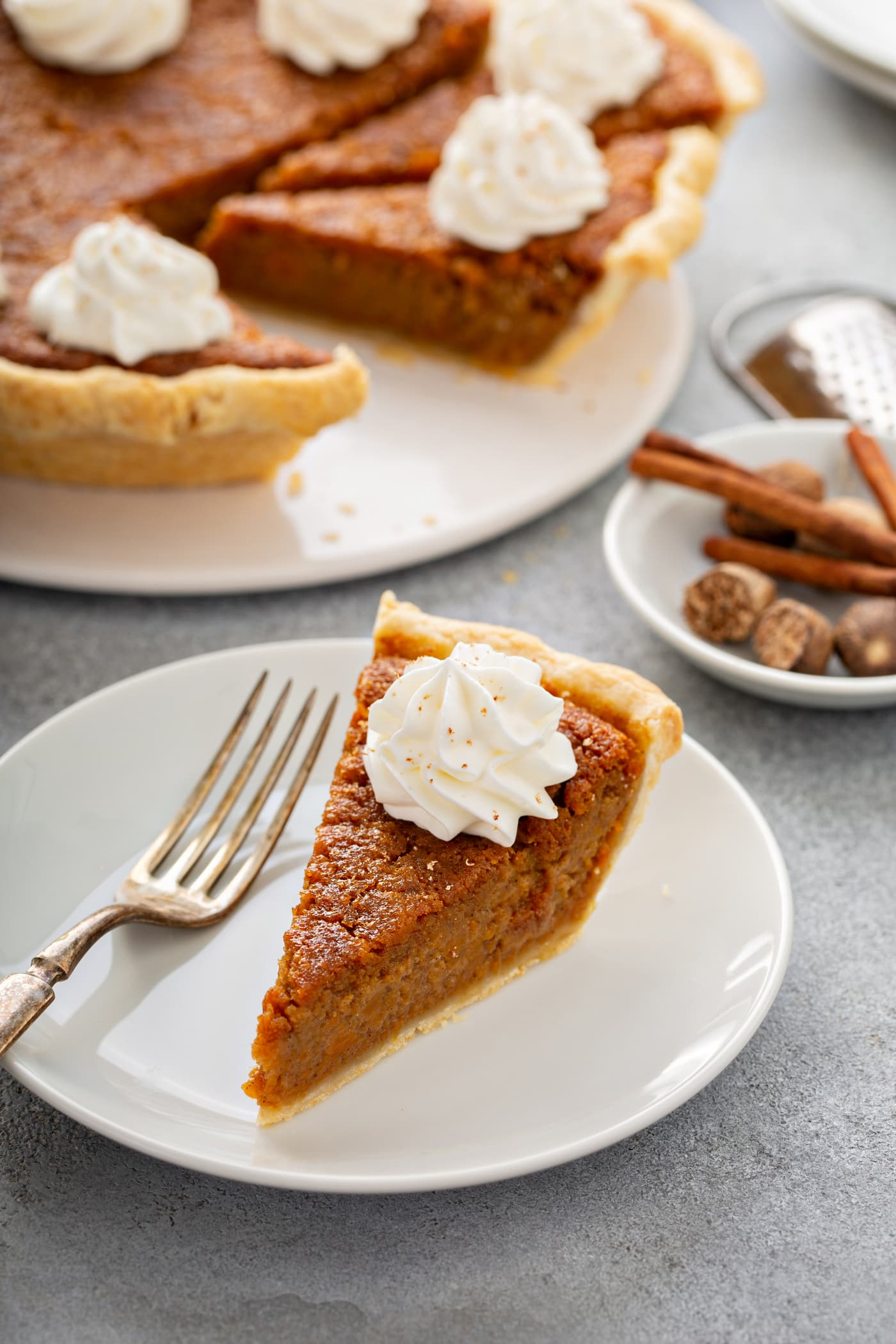 A photo of a slice of sweet potato pie sitting on a white plate with the whole sweet potato pie in the background.