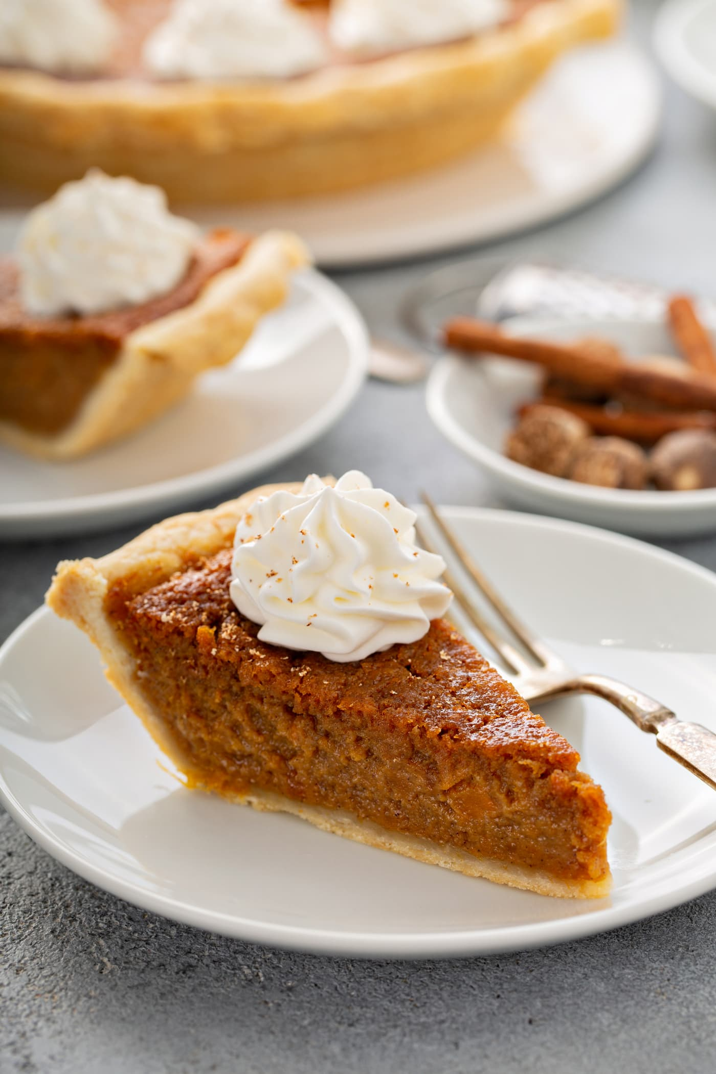 A photo of a slice of sweet potato pie with a dollop of whipped cream on top sitting on a white plate.