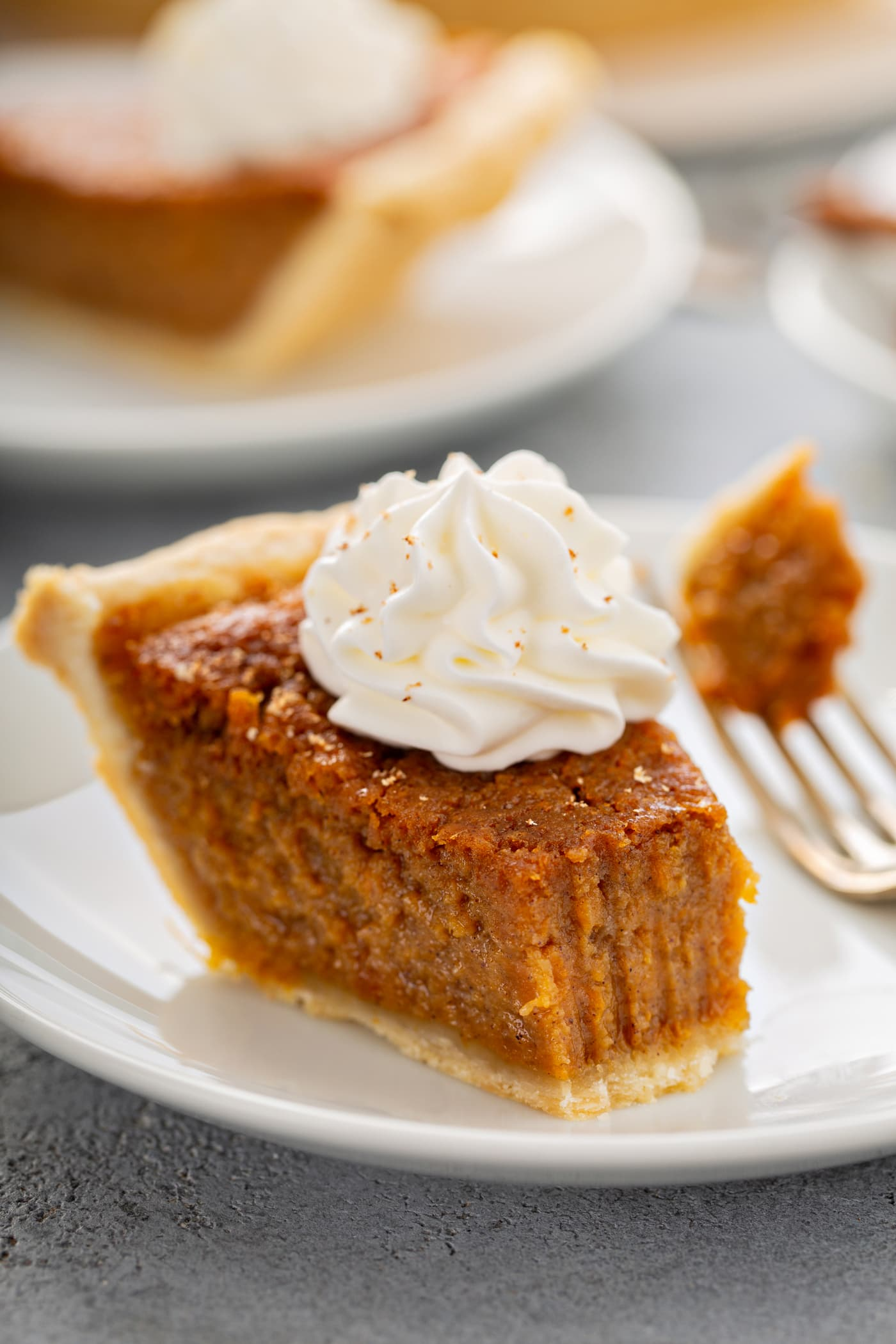 A photo of a bite of sweet potato pie being removed from a slice with a fork.