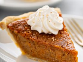 A slice of sweet potato pie with a dollop of whipped cream on top, sitting on a white plate with a fork beside it.