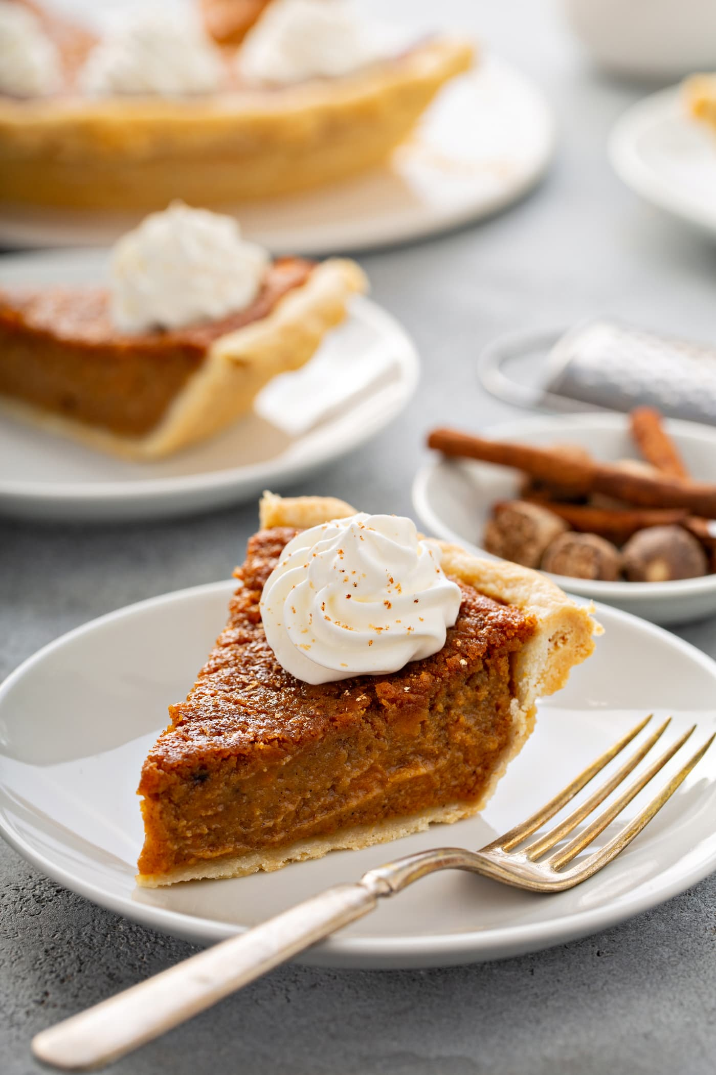 A photo of a slice of sweet potato pie sitting on a white plate with a fork sitting next to it and other servings of pie in the background.