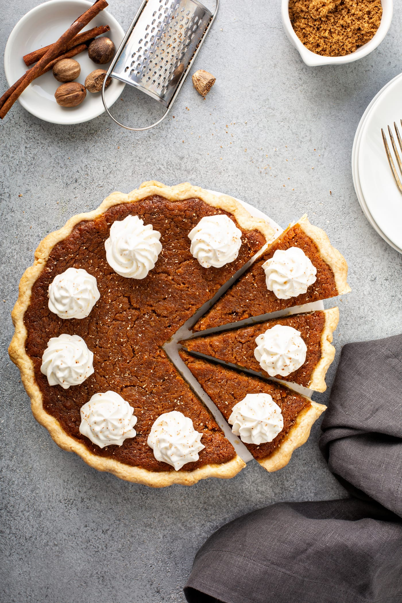 A photo of a baked sweet potato pie covered in dollops of whipped cream with three slices pulled out.