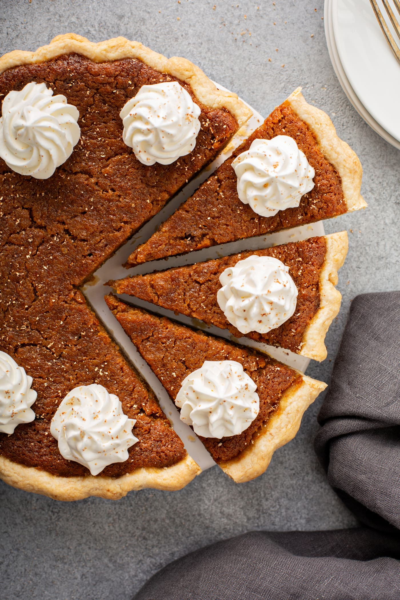 A photo of a whole sweet potato pie with dollops of whipped cream on top and three slices pulled out from the whole pie.