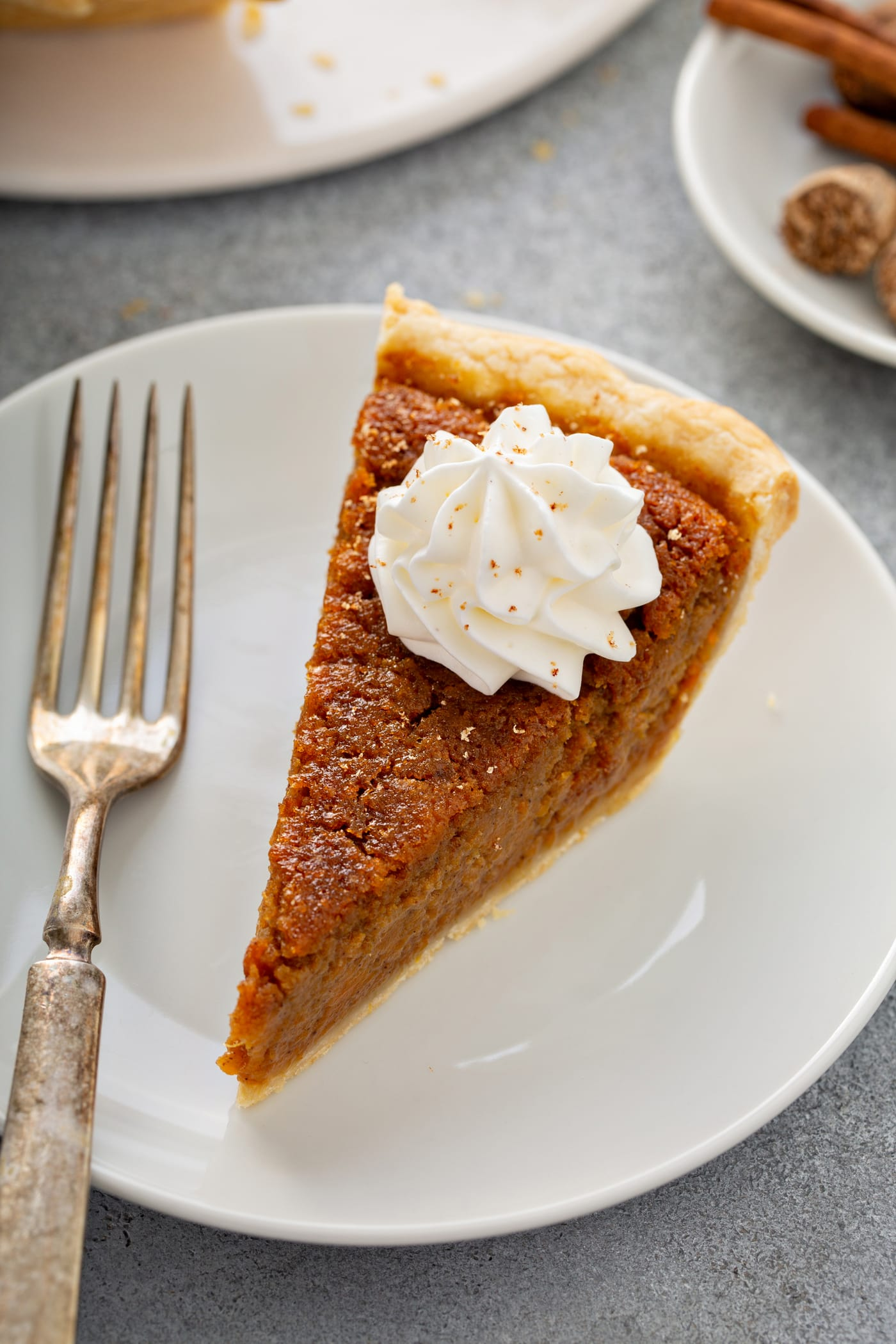 A photo of a slice of sweet potato pie sitting on a white plate with a silver fork sitting next to it.