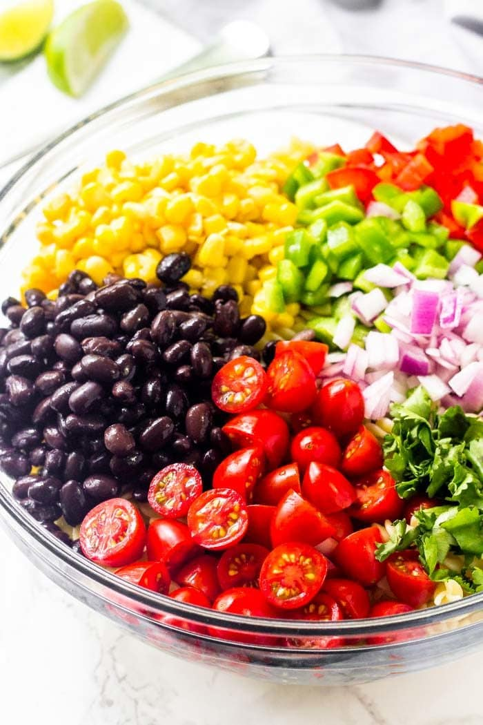 Tomatoes, black beans, corn, peppers, red onion & cilantro for making southwest pasta salad.