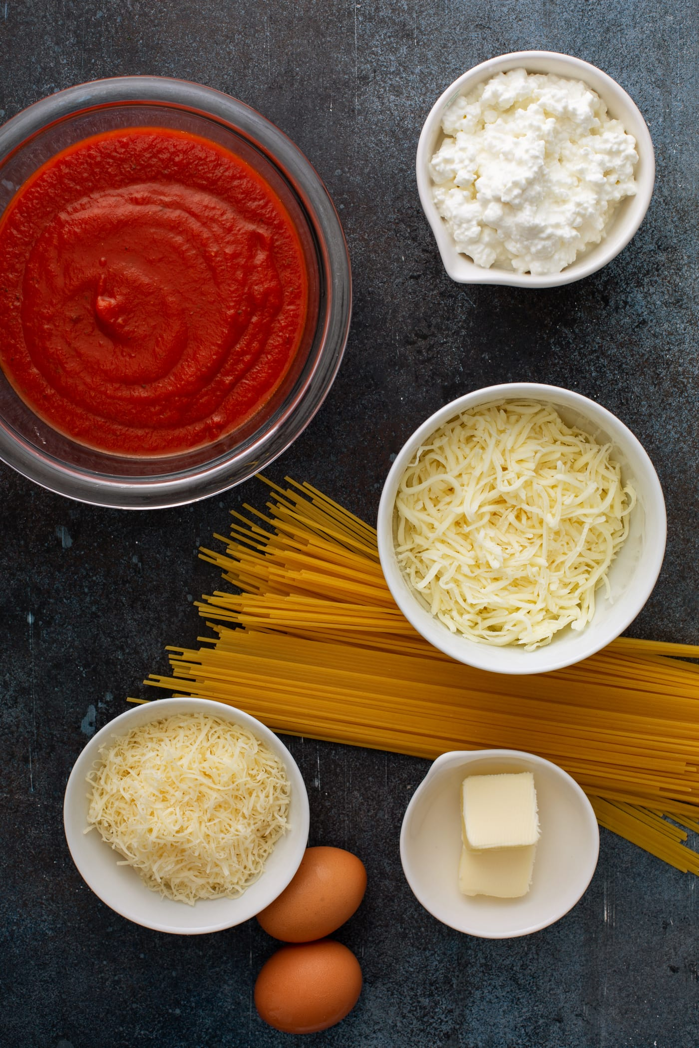 Small bowl containing ingredients for baked spaghetti pie. There is a handful of uncooked spaghetti pasta, a bowl of spaghetti sauce, small containers of shredded mozzarella cheese, cottage cheese, and Parmesan cheese.