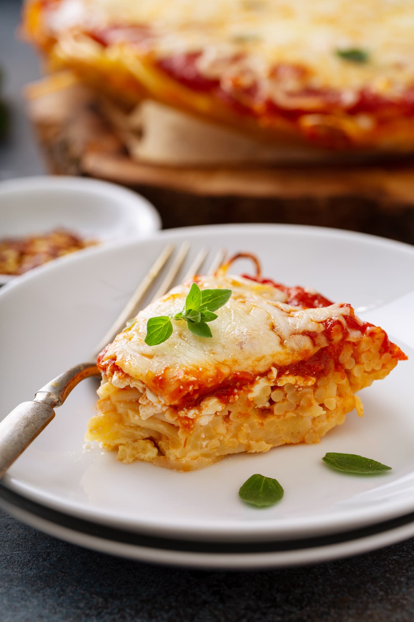 A slice of baked spaghetti pie on a white dinner plate. A fork is next to the spaghetti pie and a few basil leaves are scattered on the pie and the plate. A small container of red pepper flakes and the rest of the spaghetti pie are in the background.