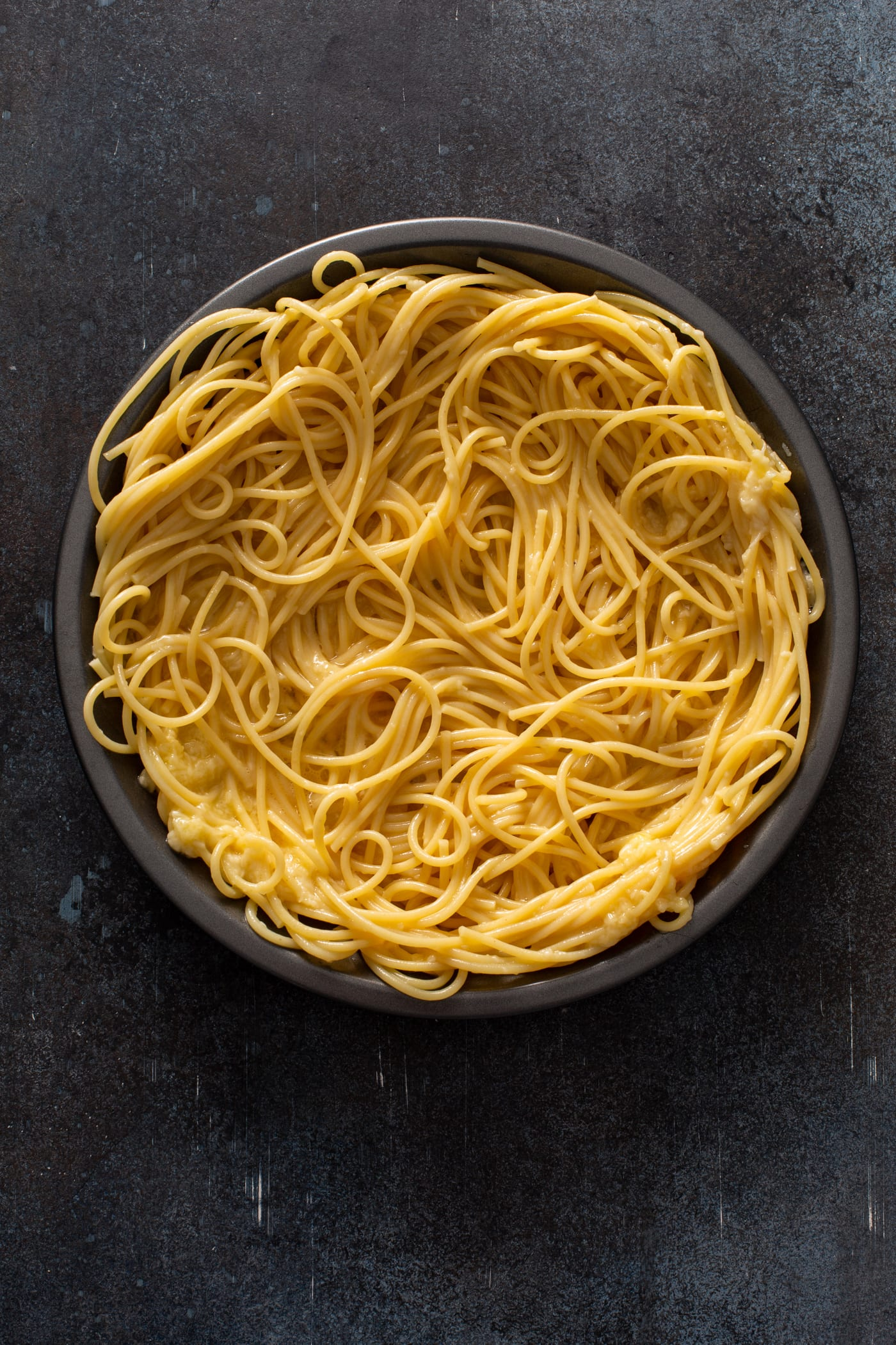 A pie dish filled with cooked spaghetti noodles.