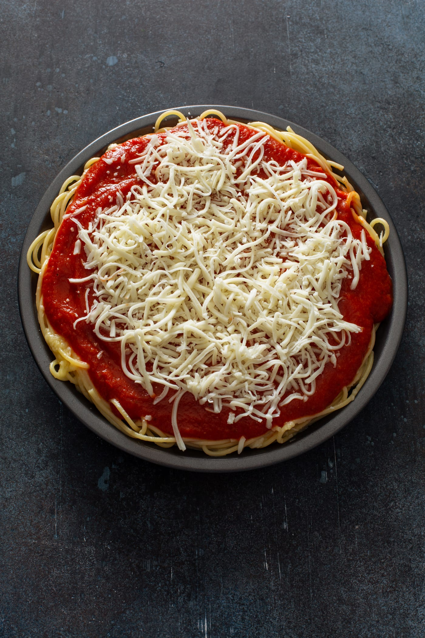 A pie dish filled with cooked spaghetti, topped with spaghetti sauce and shredded cheeses.