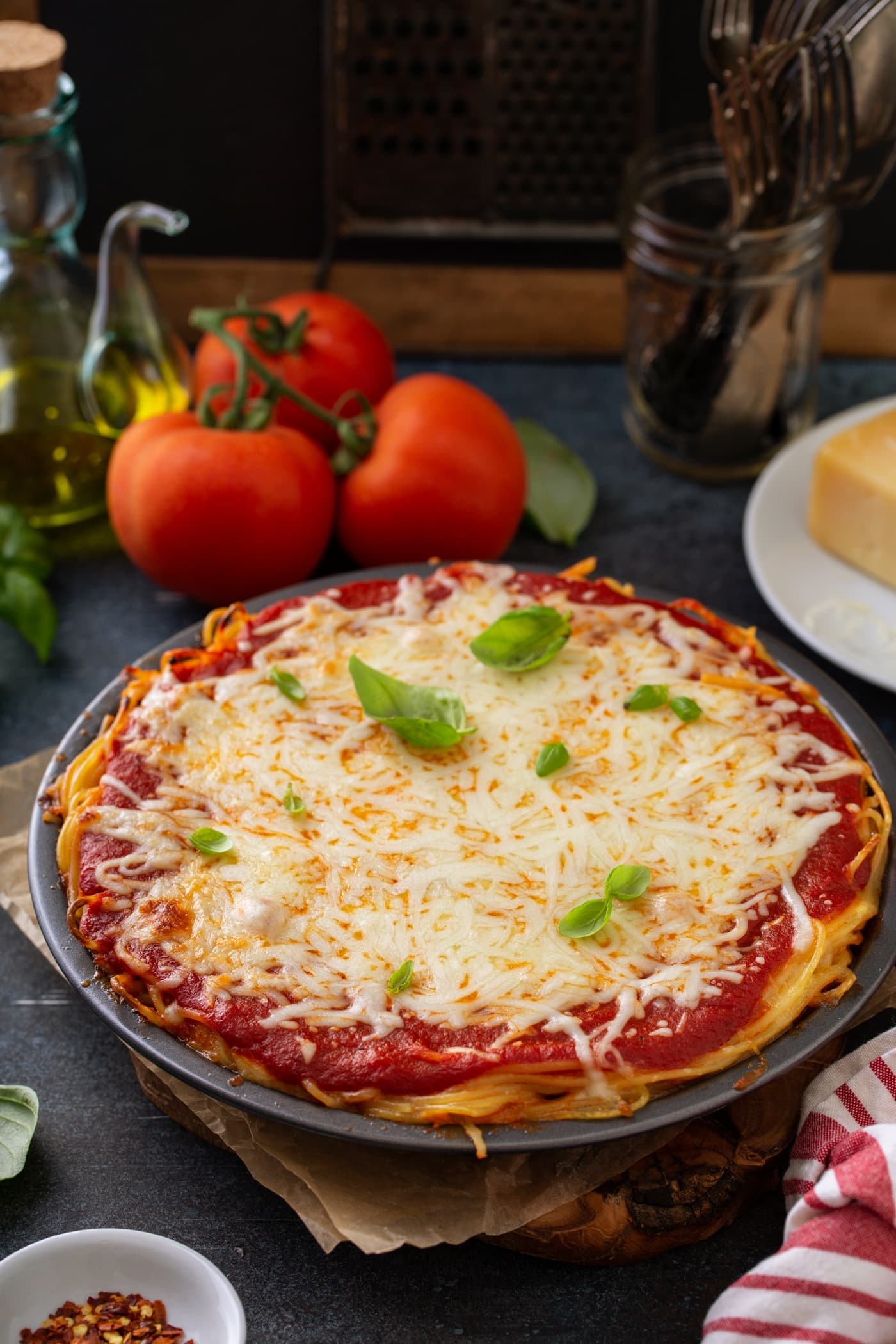 A pie dish filled with baked spaghetti pie. There are layers of spaghetti, spaghetti sauce and melted cheeses. and a few basil leaves on top. Three tomatoes, olive oil and bay leaves are in the background.