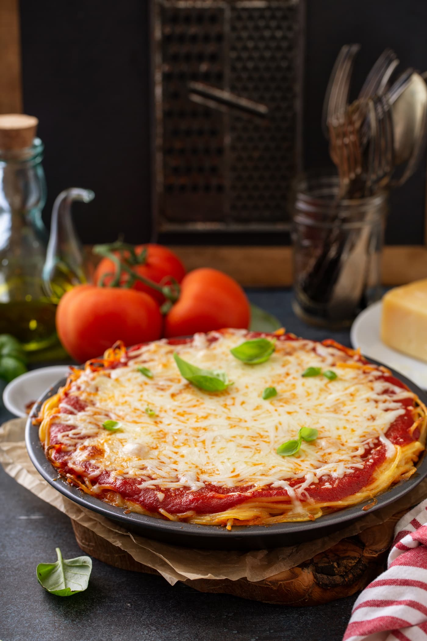 A pie dish filled with baked spaghetti pie. There are layers of spaghetti noodles, spaghetti sauce and melted cheeses. There are a few basil leaves on top and three tomatoes, olive oil, cheese, and a jar of forks in the background.