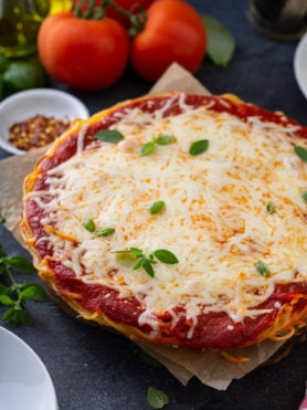 A baked spaghetti pie in a pie dish. There are layers of spaghetti, sauce, and melted cheese. Fresh basil is sprinkled on top and three tomatoes, olive oil, a container of dried red pepper flakes, and dinner plates are next to the spaghetti pie.