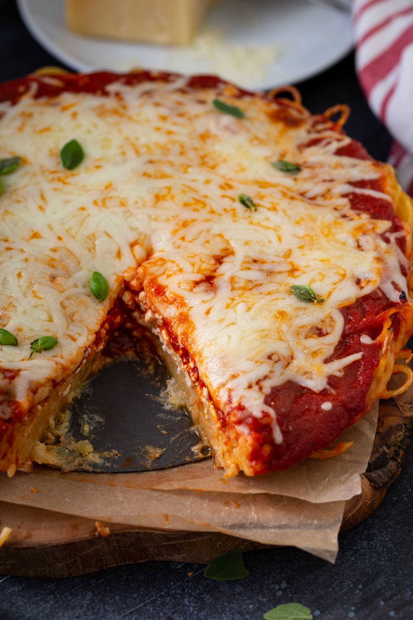 A baked spaghetti pie that has a slice removed. There are layers of spaghetti, spaghetti sauce, and melted shredded cheese. A little fresh basil is sprinkled on top.
