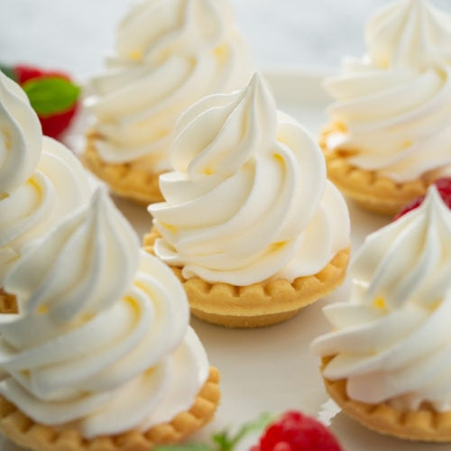 6 small tarts topped with swirled whipped cream. there are a few raspberries scattered around the tarts.