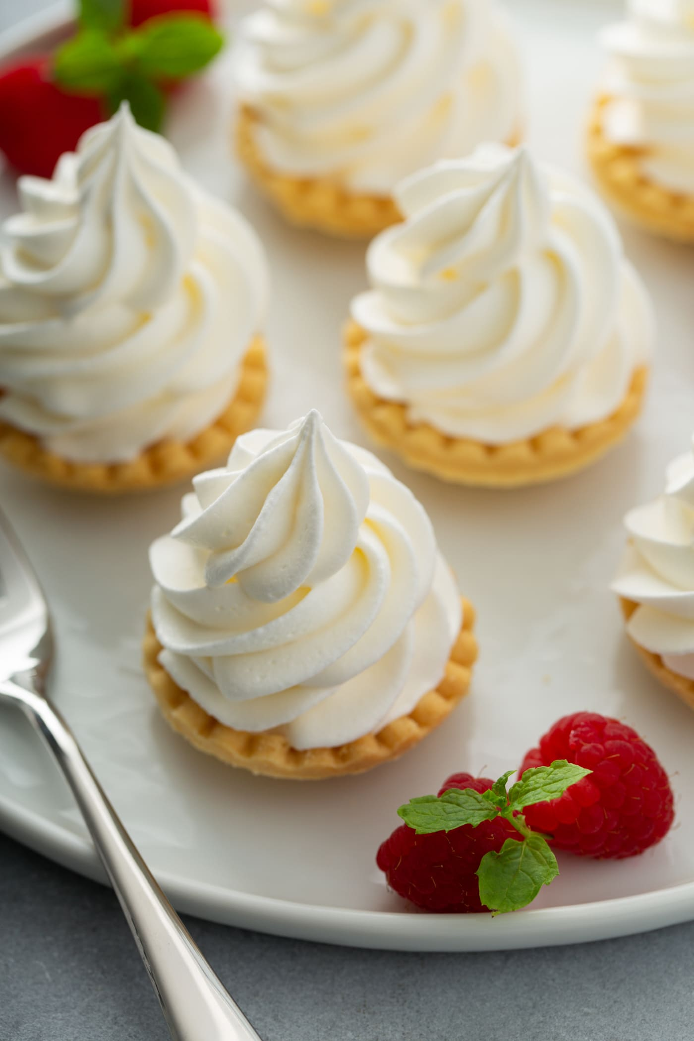 A few little tarts with whipped cream piped on top. There are a few raspberries next to the tarts.