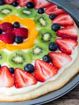 This sugar cookie fruit pizza is perfect for summer. Decorated with tangy cream cheese frosting and fresh fruit - it looks and tastes absolutely delicious.