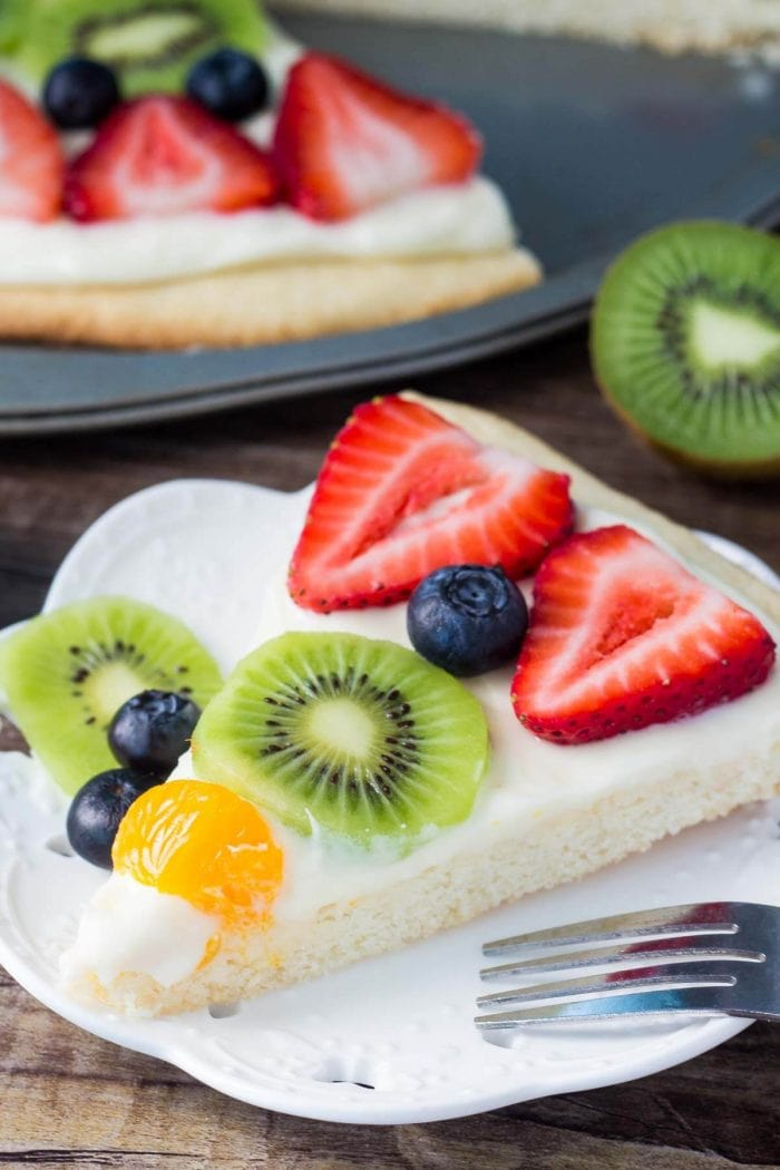 slice of sugar cookie fruit pizza on white plate with fork