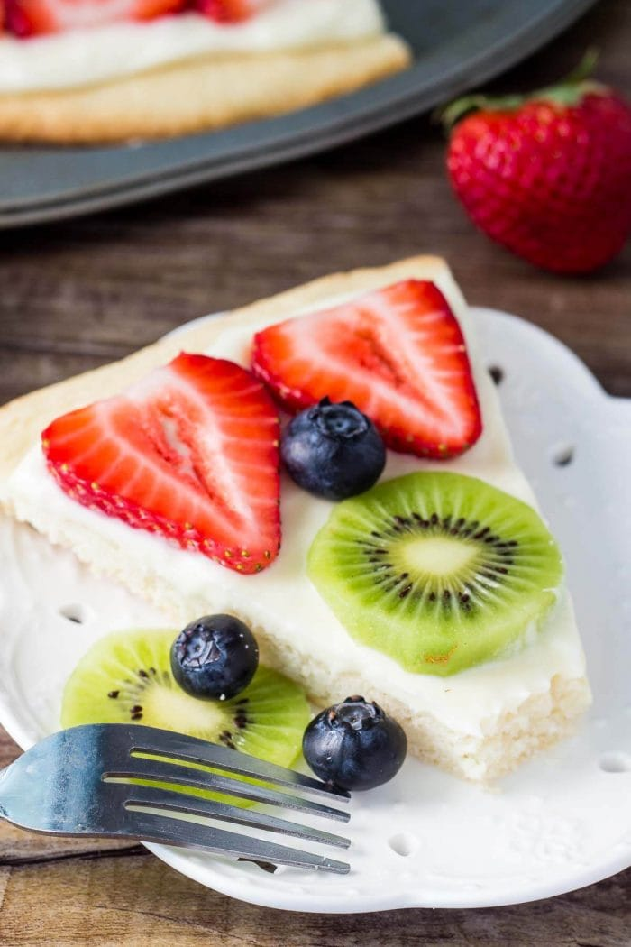 slice of sugar cookie pizza topped with fruit on white plate