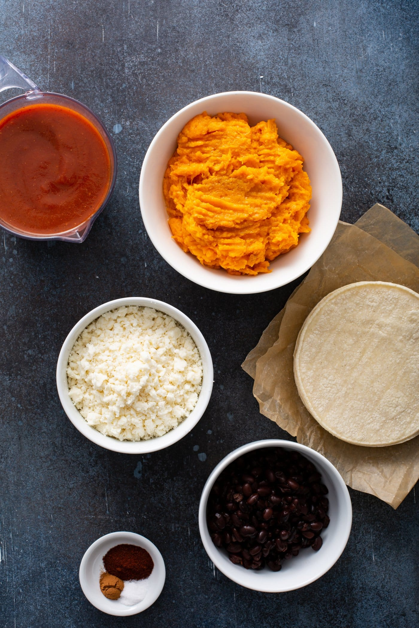 Small containers of mashed sweet potato, red enchiladas sauce, queso fresco cheese, and corn tortillas.