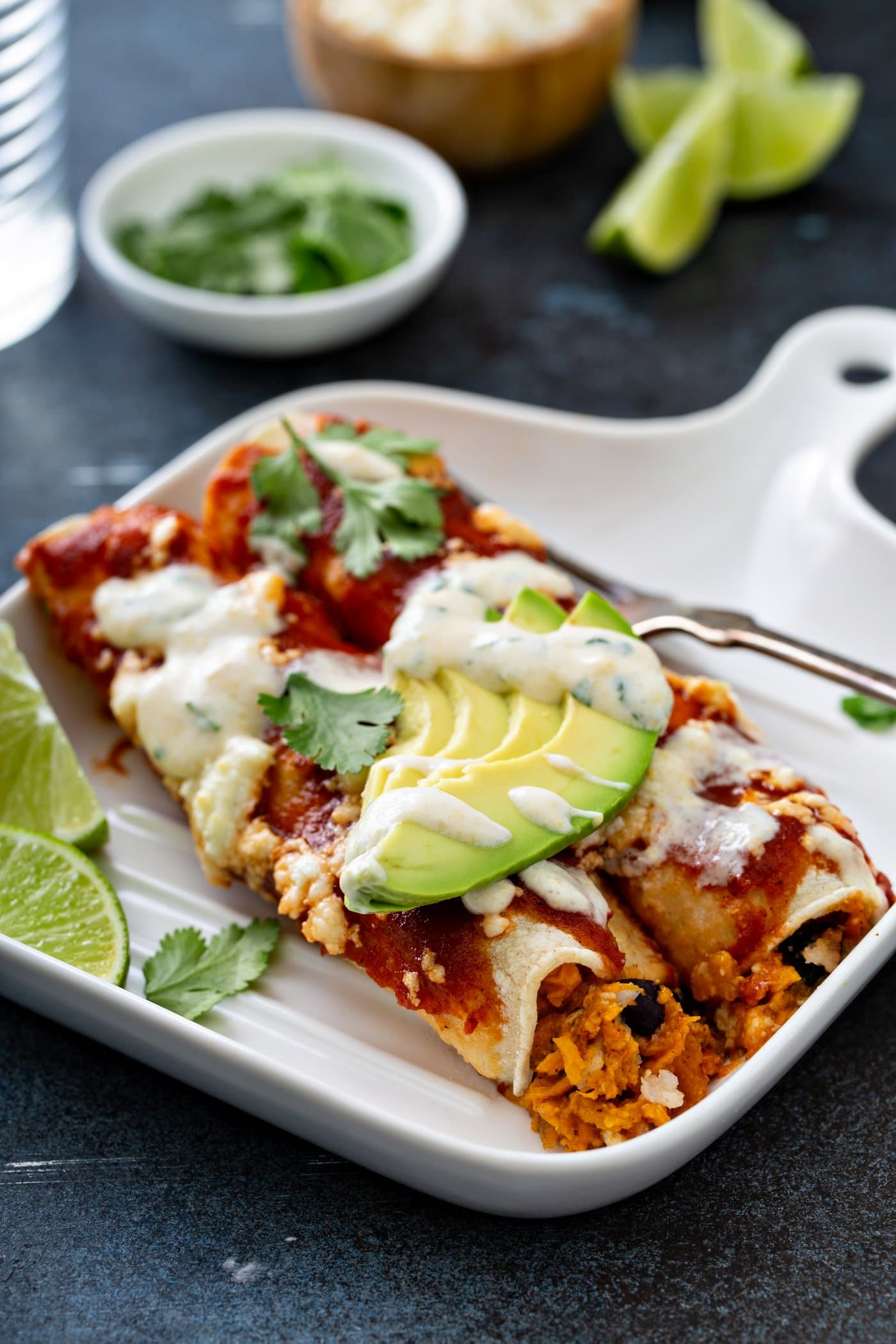 A dinner plate with two enchiladas on it. There is a fork and two lime wedges on the plate. The enchiladas have red enchilada sauce, queso fresco cheese, slices of avocado, and cilantro leaves on top. There is a sweet corn crema drizzled over the top of it.