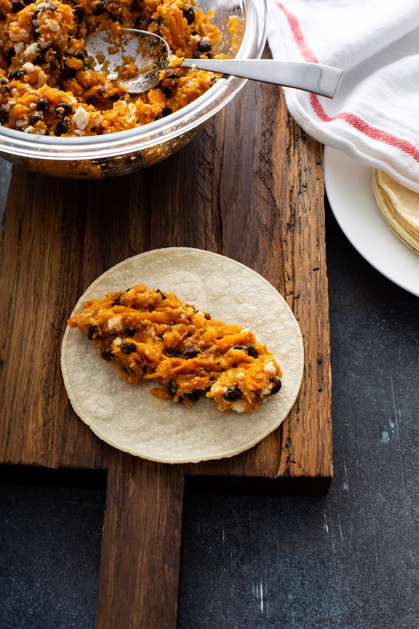 Sweet potato filling with beans and cheese on an open corn tortilla. There is a bowl of enchilada filling and a plate of corn tortillas covered with a red and white kitchen towel in the background.