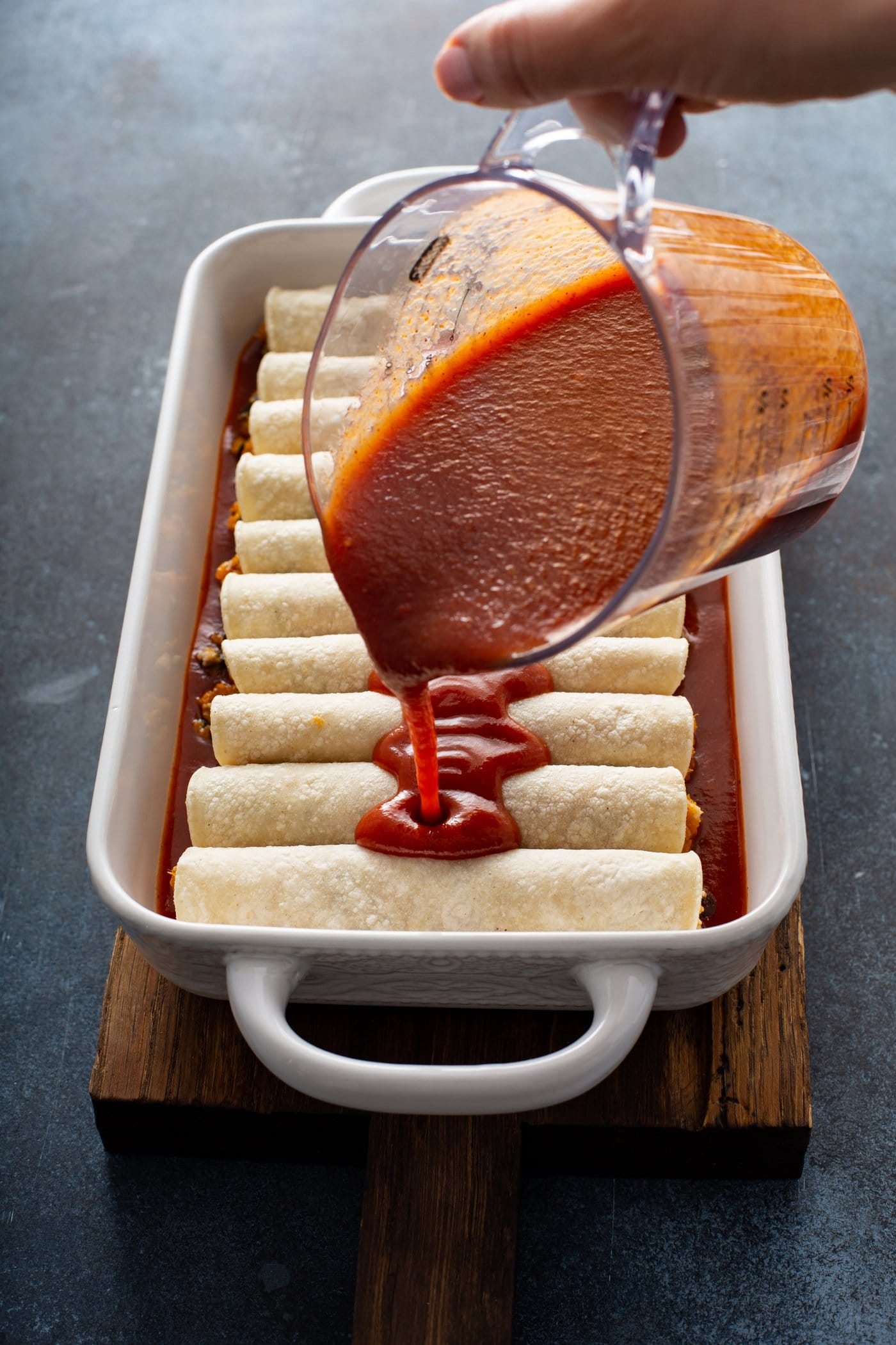 Unbaked enchiladas in a white baking dish. Red enchilada sauce is being poured from a glass measuring cup over the enchiladas.