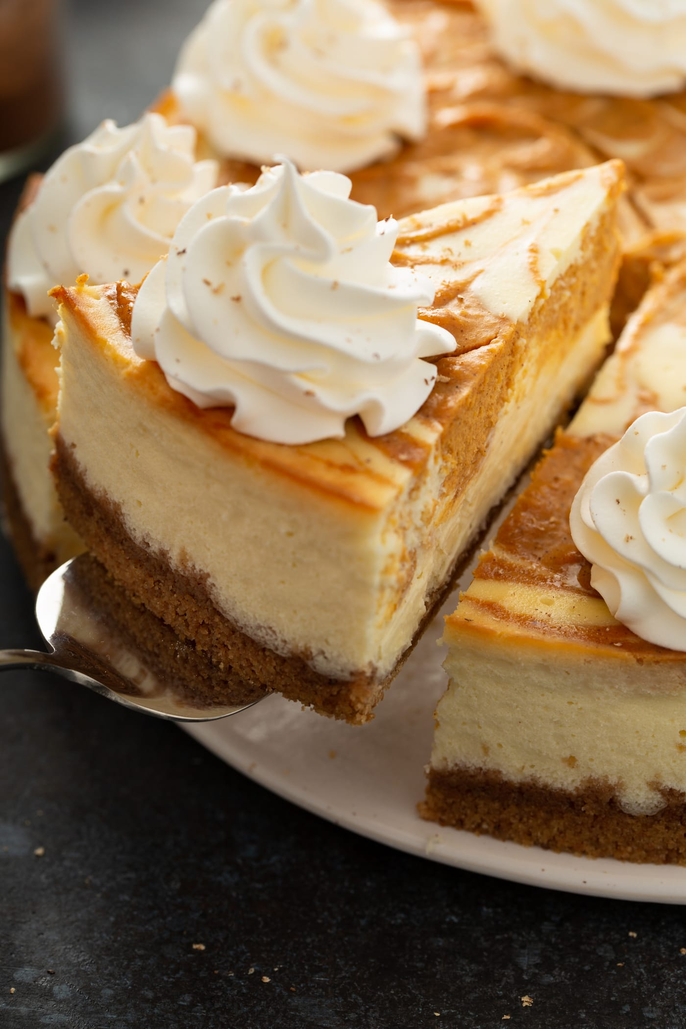 A slice of swirled pumpkin cheesecake being lifted from the whole cheesecake. It has a graham cracker crust and pumpkin filling is swirled into the cheesecake. A dollop of whipped cream is on top.