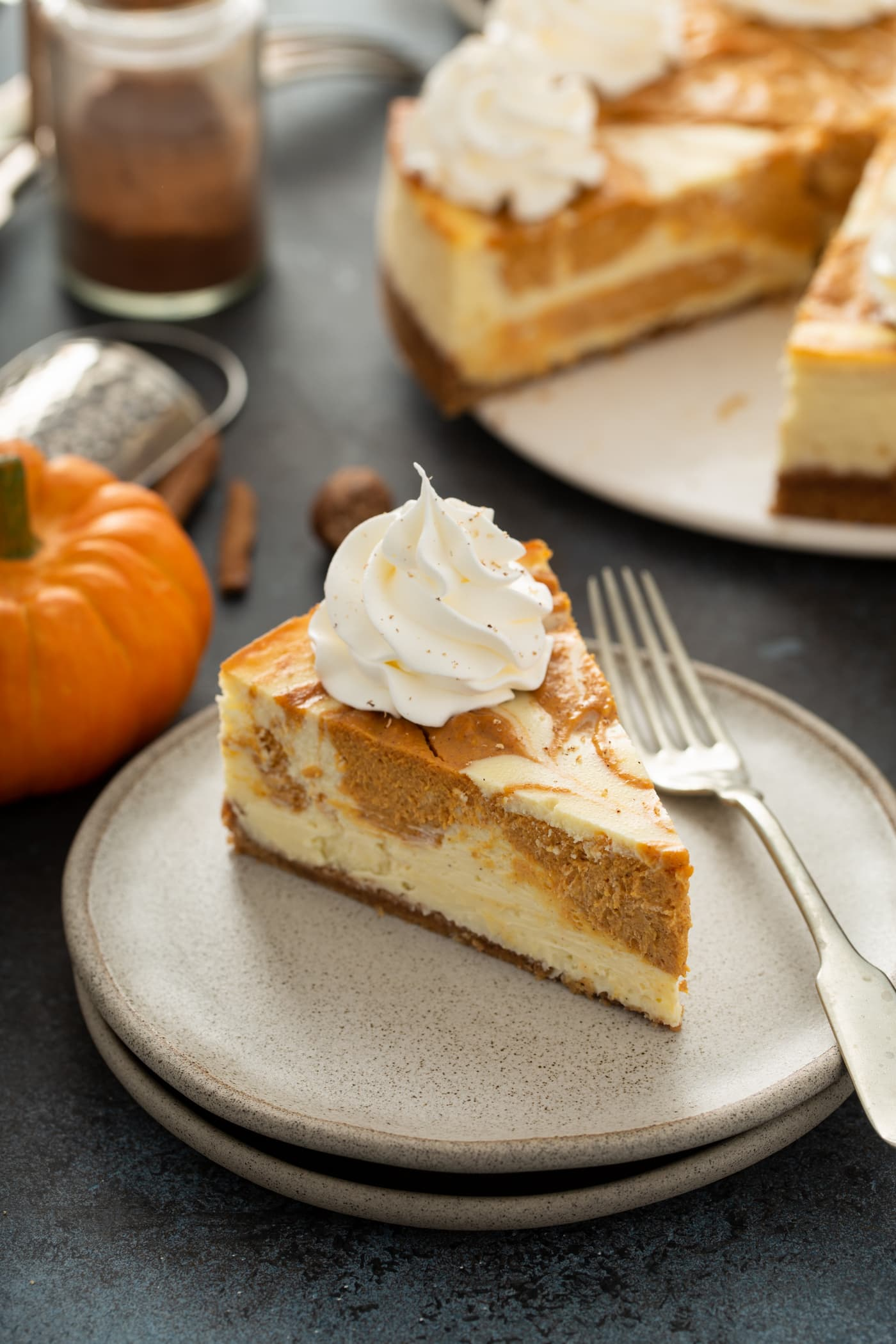 A slice of swirled pumpkin cheesecake on a dessert plate with a fork. The rest of the cheesecake, and a small pumpkin are in the background.