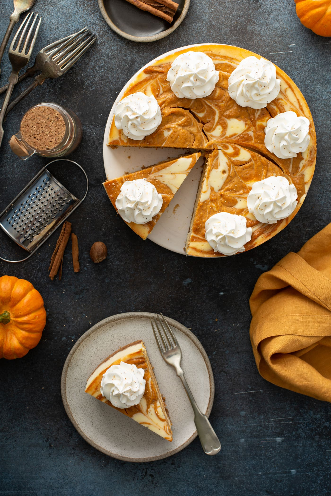 A plate with a slice of swirled pumpkin cheesecake and a fork. The rest of the cheesecake is in the background with cinnamon sticks, a small pumpkin and an orange napkin.