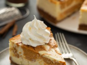 A slice of swirled pumpkin cheesecake on a plate with a fork. The rest of the cheesecake is in the background.