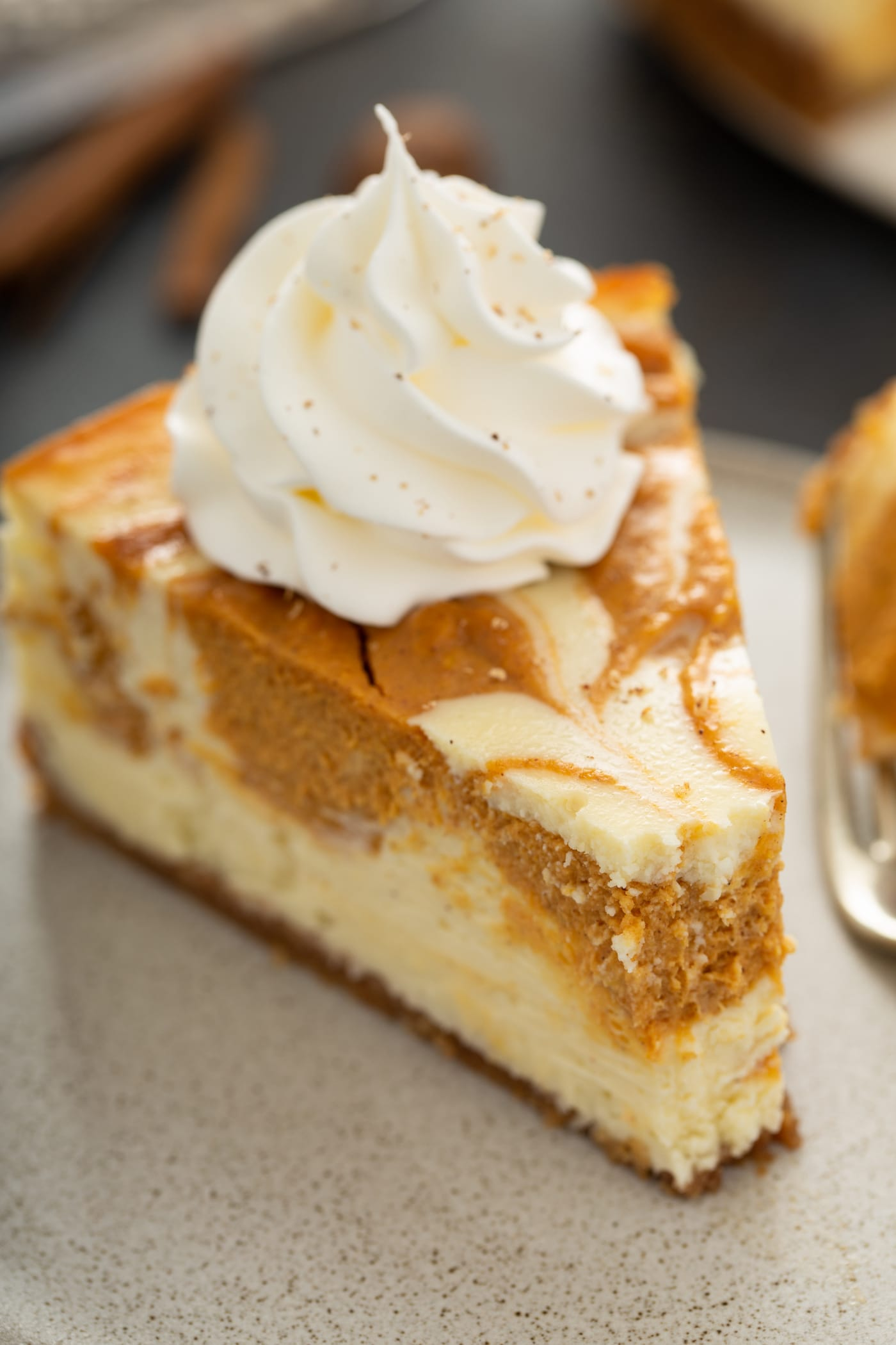 A piece of swirled pumpkin cheesecake on a plate. It is topped with a dollop of whipped cream and a bite has been taken from the point of the slice.