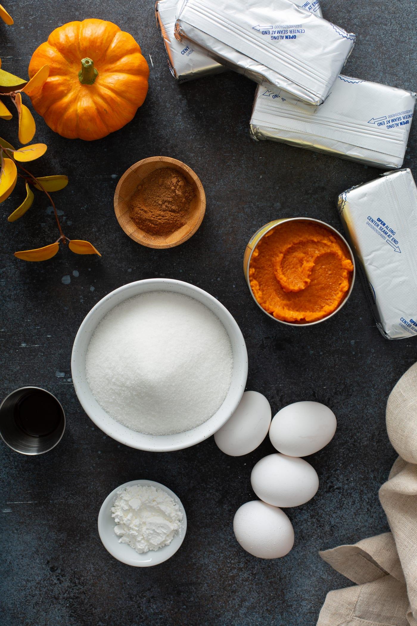 Ingredients for swirled pumpkin cheesecake. There is sugar, eggs, pumpkin, cinnamon, cream cheese, and vanilla.