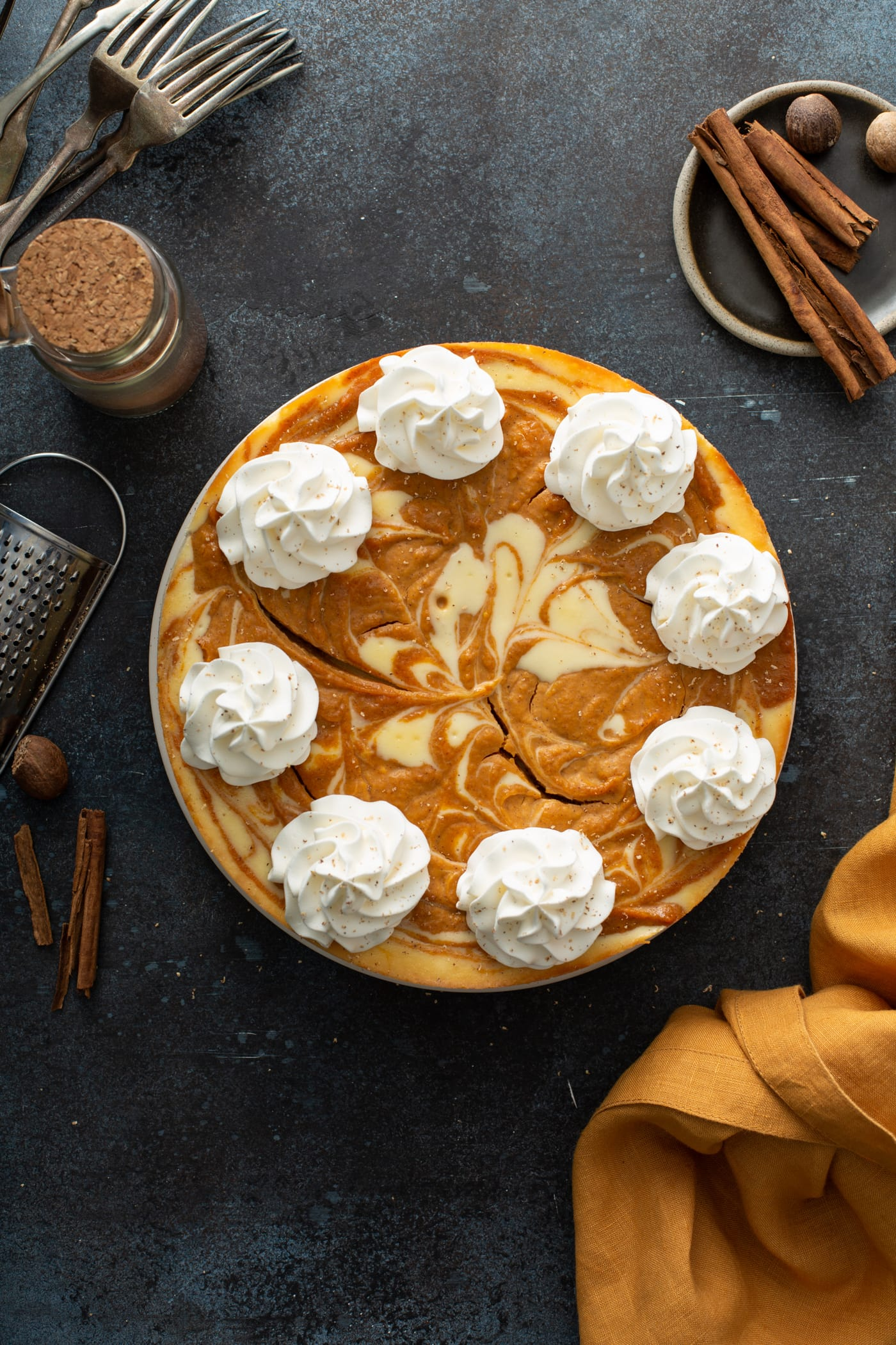 A swirled pumpkin cheesecake topped with dollops of whipped cream.
