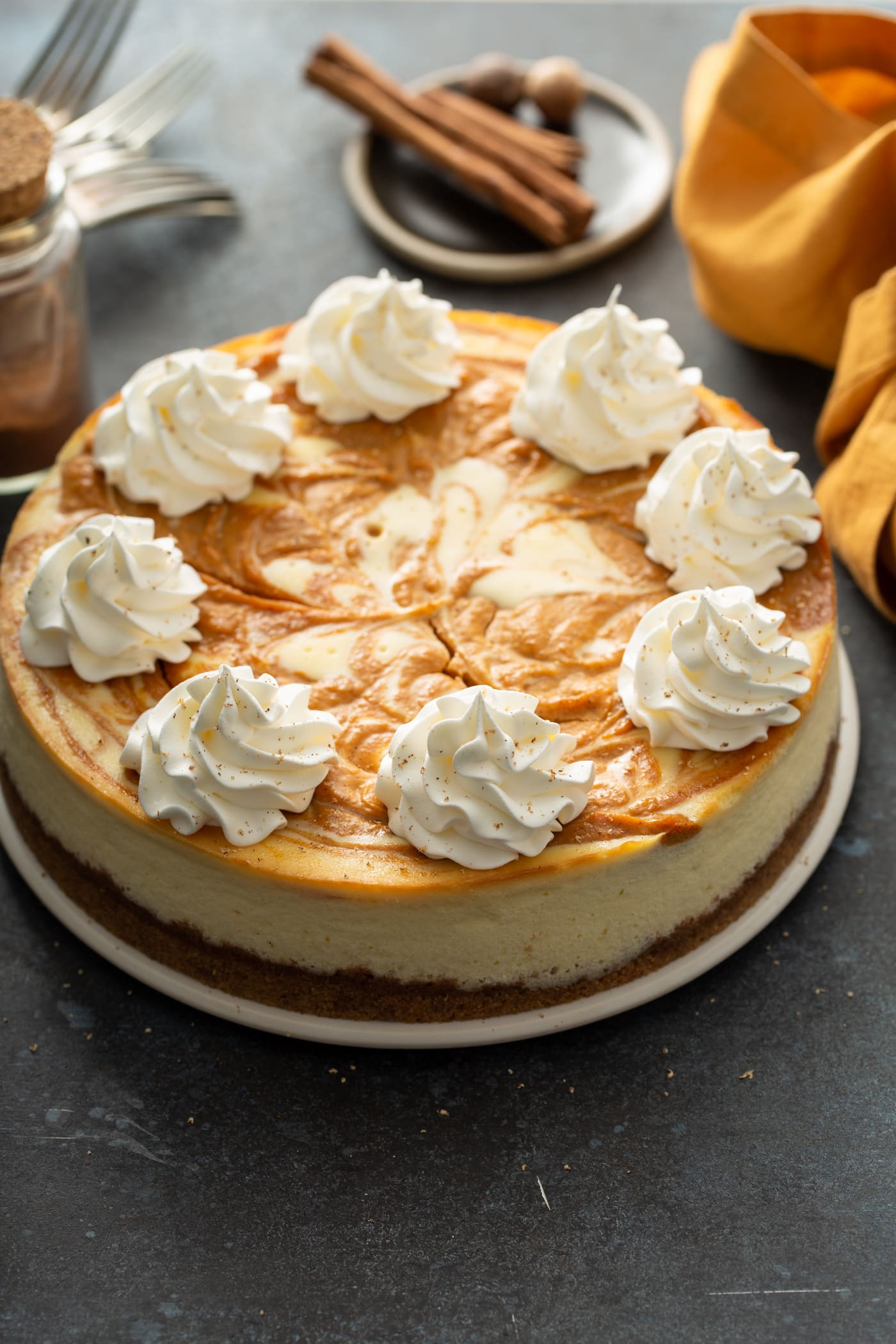 A whole swirled pumpkin cheesecake topped with dollops of whipped cream. There is a napkin, cinnamon sticks and whole nutmeg in the background.